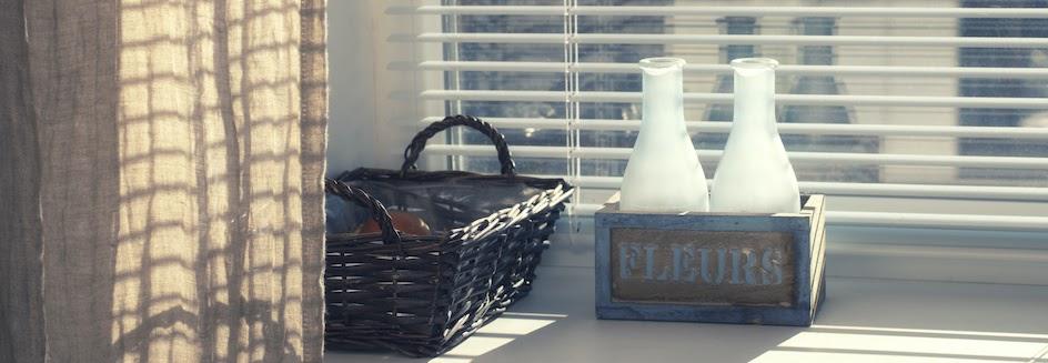Horizontal blinds behind glass bottles