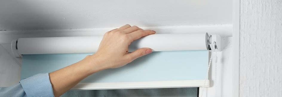 Hand putting up a roller blind