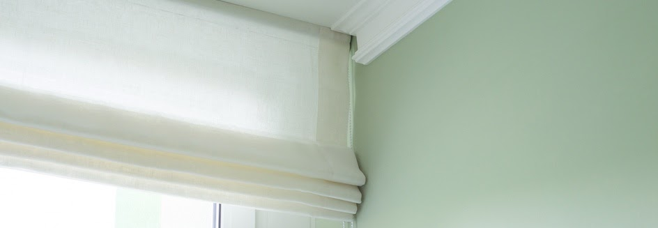 White roman blinds rolled up
