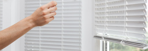 Person pulls cord on white venetian blinds