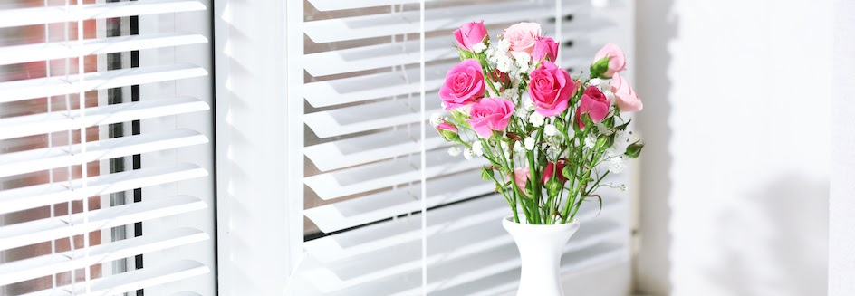 White wooden blinds behind pink flowers in vase