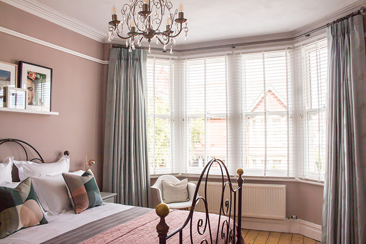 bedroom with white venetian blind in a bay window