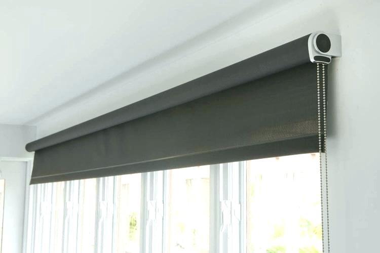 black roller blind rolled up in window frame