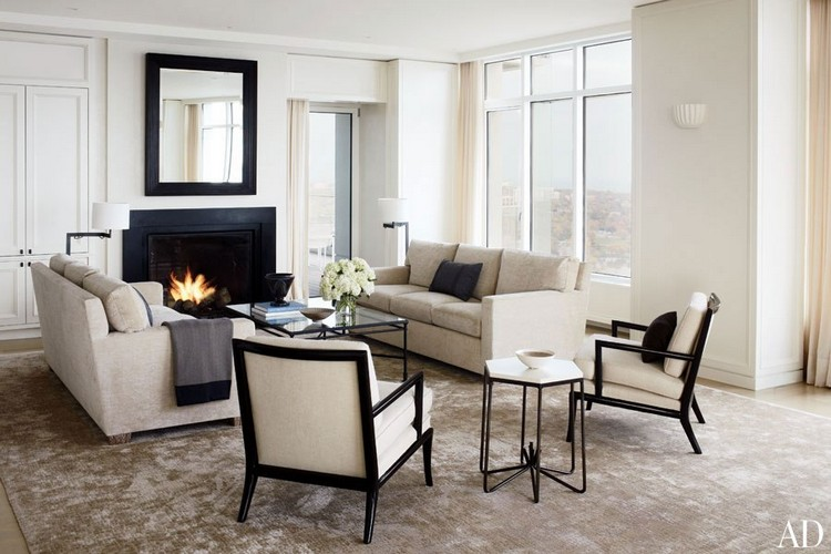 white living from with fire place surrounded by a sofa and chairs